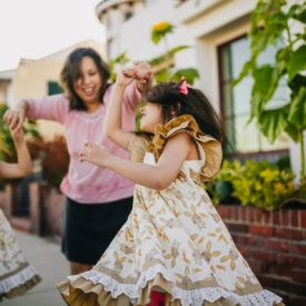mother dancing with her daughters on the street